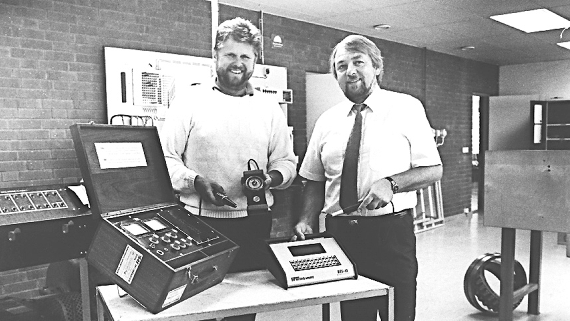 Two SPM representatives showing measuring instruments from SPM in the early days